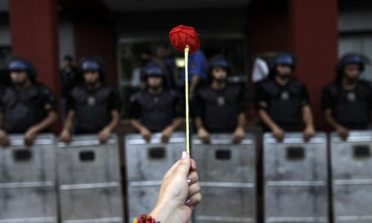 An activists holds up a flower in front of police officers during a demonstration marking the International Human Rights Day in Asuncion, Paraguay.