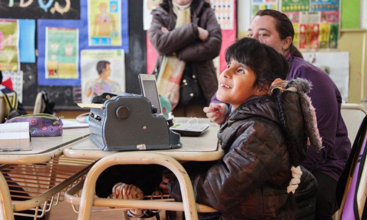Agustina, 9, Arjantin, Córdoba'daki sınıfında bir Perkins Brailler ve erişilebilir bir dizüstü bilgisayar kullanıyor. (© Brian Messenger / Perkins Körler Okulu)