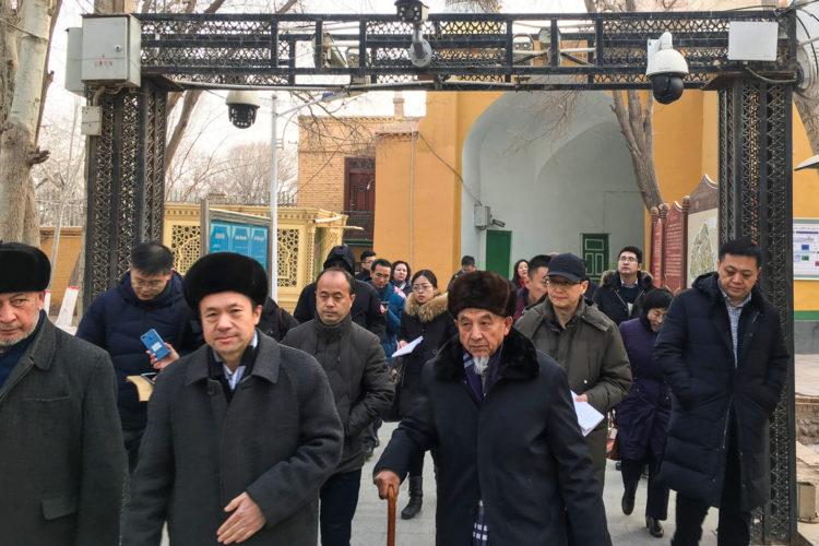 İmamlar ve hükümet yetkilileri, Ocak 2019'da Çin'in Sincan Uygur Özerk Bölgesi'nde bulunan Kaşgar'daki Iydgâh Camii'nden ayrılırken güvenlik kameraları altından geçiyorlar. (© Ben Blanchard/Reuters)